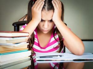 Angry and tired schoolgirl studying with a pile of books on her desk. 15 Smart Strategies to Surviving a Bad Teacher