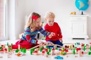 Two children playing with toys in a bedroom. 37 Ways to Help Your Child be School Ready
