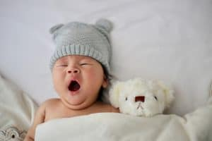 Baby yawning while in bed with a teddy bear. 7 Easy Ways to Get Your Baby to Sleep Through the Night