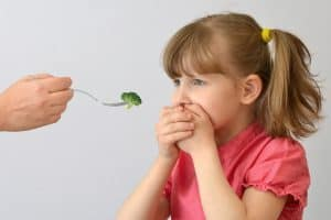 Little girl in a red shirt holding hands over her mouth as she is being fed broccoli on a fork by a woman's hand.