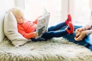 Mom sitting on bed watching her pre-schooler read a book 9 Sneaky Ways Your Pre-Schooler is in Charge and How to Fix It