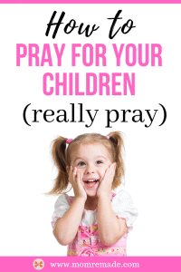 Little girl in pink with her hair in pig tails and hands on face with a big smile.