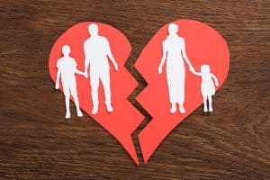 Paper heart broken in half with family members in a cut out on it. How to Break Free From Family Issues For