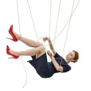 Woman in blue dress and red shoes hanging in the air with strings tied to her like a puppet with text overlay.