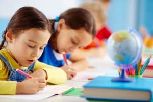 Children sitting at a desk writing on paper. 9 Best Character Qualities Your Child Needs at School
