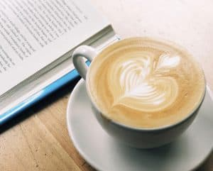 Cup of coffee and a book on a table. 25 Powerful Quotes to Inspire You to Live Your Best Life